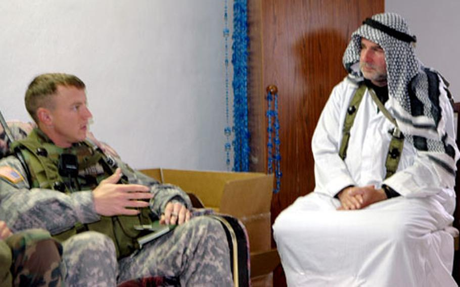 Let's make a deal: Capt. Chris Kuzio talks business with the fake sheik of the fake village of Rusafa, during a 1st Armored Division training exercise at Hohenfels.