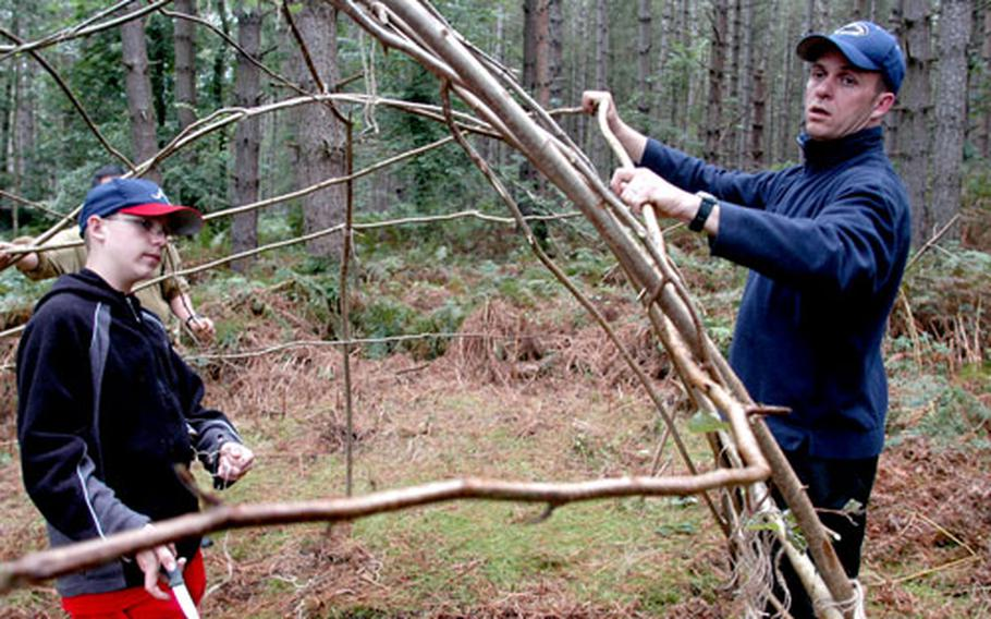 Tech. Sgt. Dan Kent, of the 100th Communications Squadron at RAF Mildenhall, builds a shelter out of hazel trees with his son, Daniel, during a weekend camping trip.