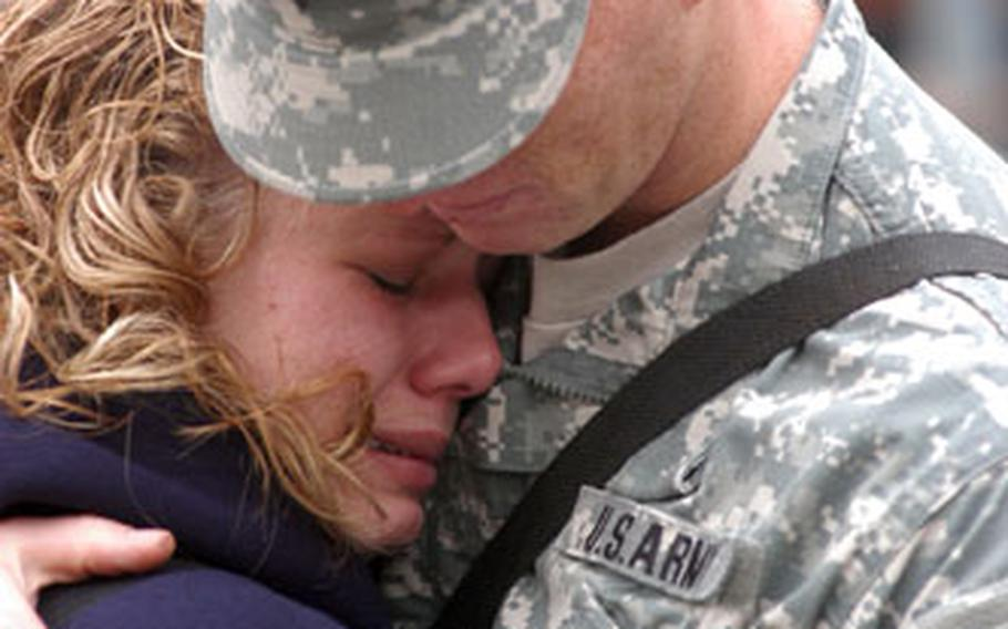 Spc. James Becker hugs wife Ashley as they say goodbye Wednesday at Cambrai-Fritsch Casern in Darmstadt, Germany. Becker and about 400 other soldiers of the 22nd Signal Brigade departed Darmstadt to serve in Operation Iraqi Freedom.
