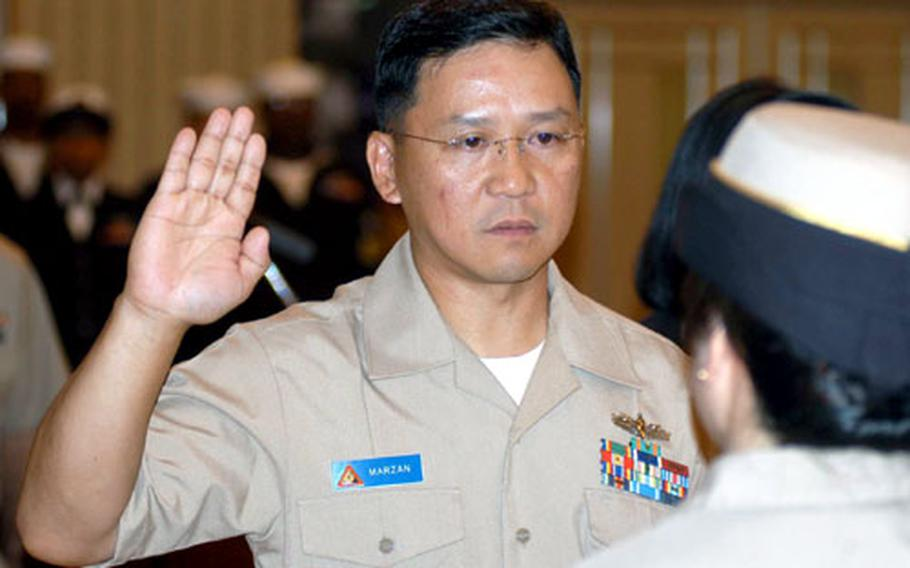 Julius Arturo C. Marzan is sworn in as a chief warrant officer during a commissioning ceremony Wednesday at Misawa Air Base, Japan. Marzan was one of two enlisted supply experts in his category to be selected to the Navy's chief warrant officer program this year.