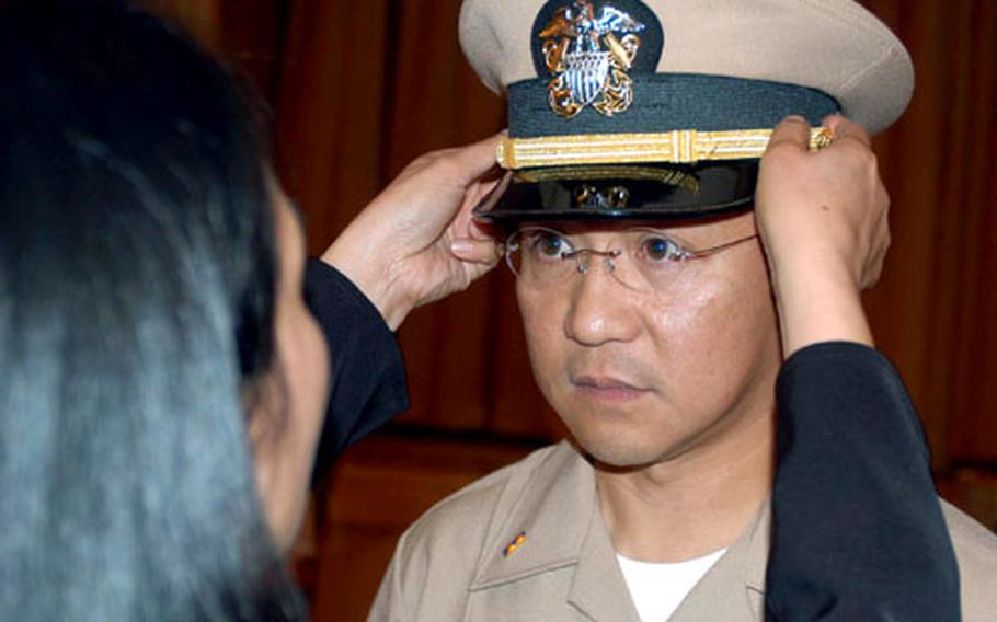 Elizabeth Marzan places a naval officer cap on her husband, Julius Arturo C. Marzan, during his chief warrant officer commissioning ceremony at Misawa.