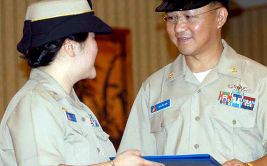 Navy Cmdr. Ann Kubera, commanding officer of Personnel Support Activity-Pacific, hands Julius Arturo C. Marzan his honorable discharge papers at Marzan's commissioning cermony Wednesday at Misawa.