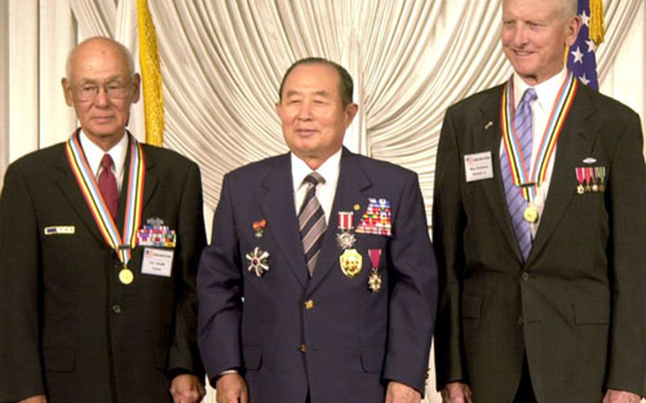 """From left, retired Col. Toshio Aoyahi, Korean Veterans Association chairman Lee Sang-hoon and retired Maj. Gen. Kenneth E. Dohlman stand after Lee awarded the two retired soldiers """"ambassador of peace"""" medals during a dinner Tuesday in Seoul."""