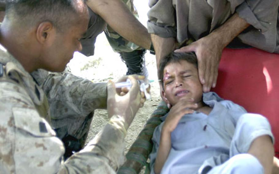 U.S. Navy Corpsman Eric Eberdong flushes out the head wound of an Afghan child Monday in the eastern Afghanistan village of Watapoor. Eberdong was attached to 3rd Platoon, Company E, 2nd Battalion, 3rd Marine Regiment, 3rd Marine Division for a five-day patrol. The child fell while running.
