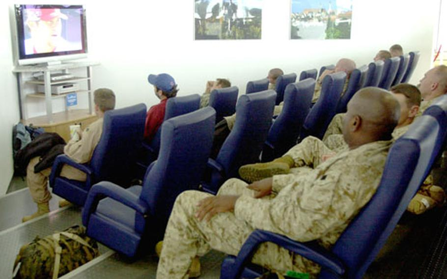 Servicemembers watch the baseball playoffs from the United Services Organization's lounge's theater Thursday at Ramstein Air Base's passenger terminal.;