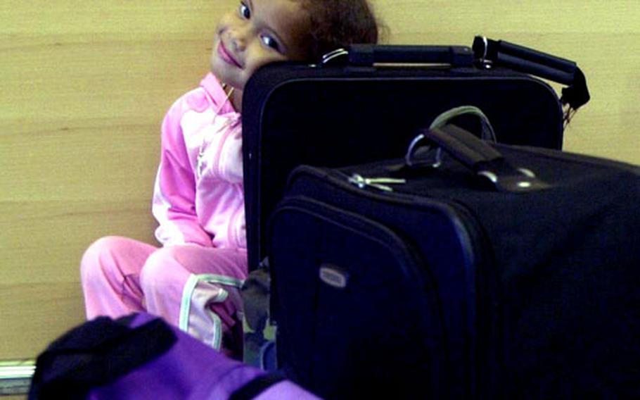 Danielle Fleming, 4, rests her head on her family's luggage Thursday at the newly opened baggage claim area at the Ramstein Air Base passenger terminal.