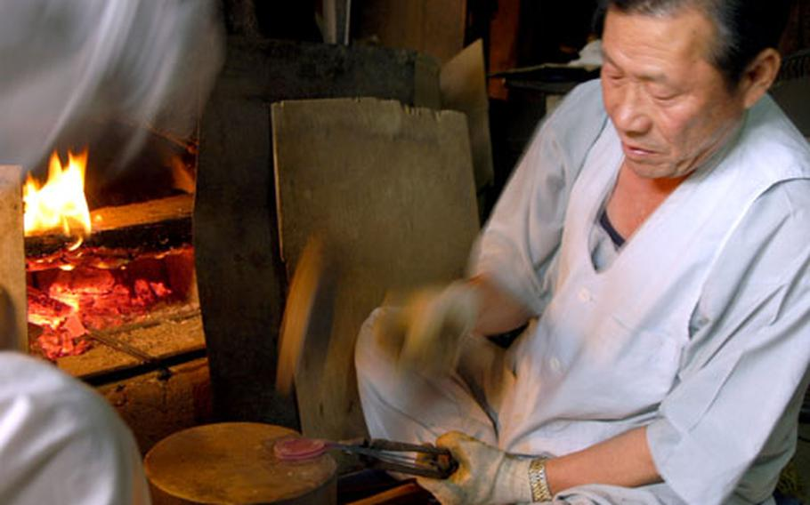 """On """"workshop street,"""" men use fire and mallets to shape metal into spoons. Other exhibits include silk-spinning, paper-making, embroidery and cooking."""