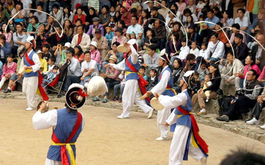 Hundreds of people gather to watch a traditional farmers' dance at the performing area in the Korean Folk Village.