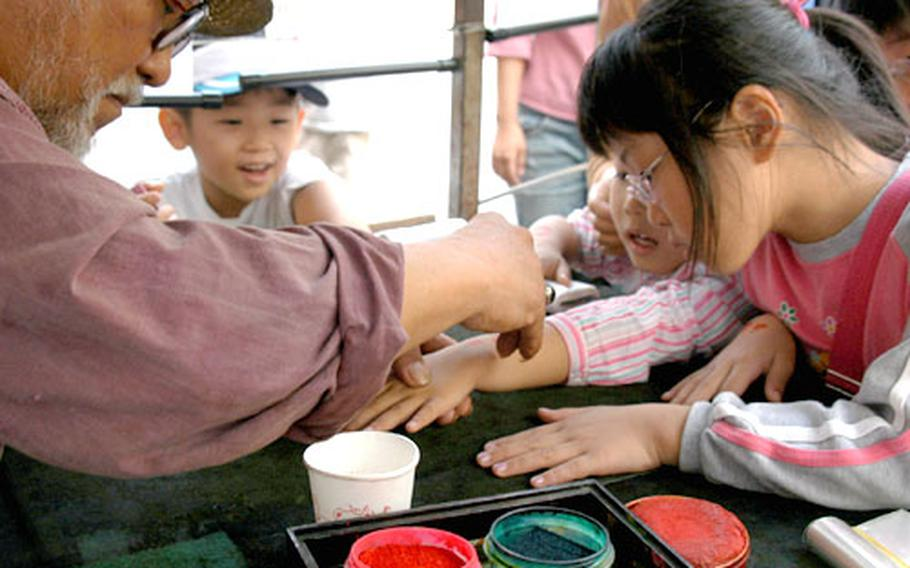 The Korean Folk Village is very child friendly. Here, a man draws Korean figures on kids' arms for free.