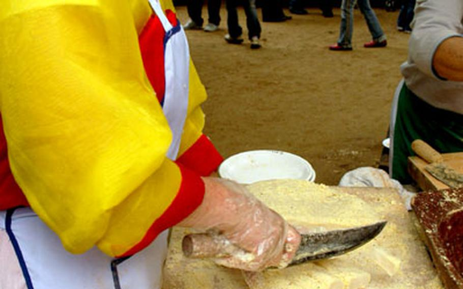 A woman in the Korean Food Court cuts a rice cake for customers. The food court has dozens of traditional Korean dishes for sale. To purchase a meal, go to one of the outer cashier booths and place your order (there are English menus), then proceed to the various food booth to pick up your lunch.