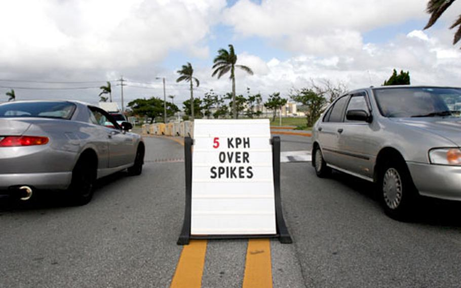 A sign cautions motorists traveling in and out of Gate 1 at Camp Foster, Okinawa, to drive 5 kph when driving over security spike strips and metal barriers. Base officials posted the signs in late September in response to several incidents in which vehicles were damaged by security spike strips or metal barriers at Okinawa Marine Corps base entrances.
