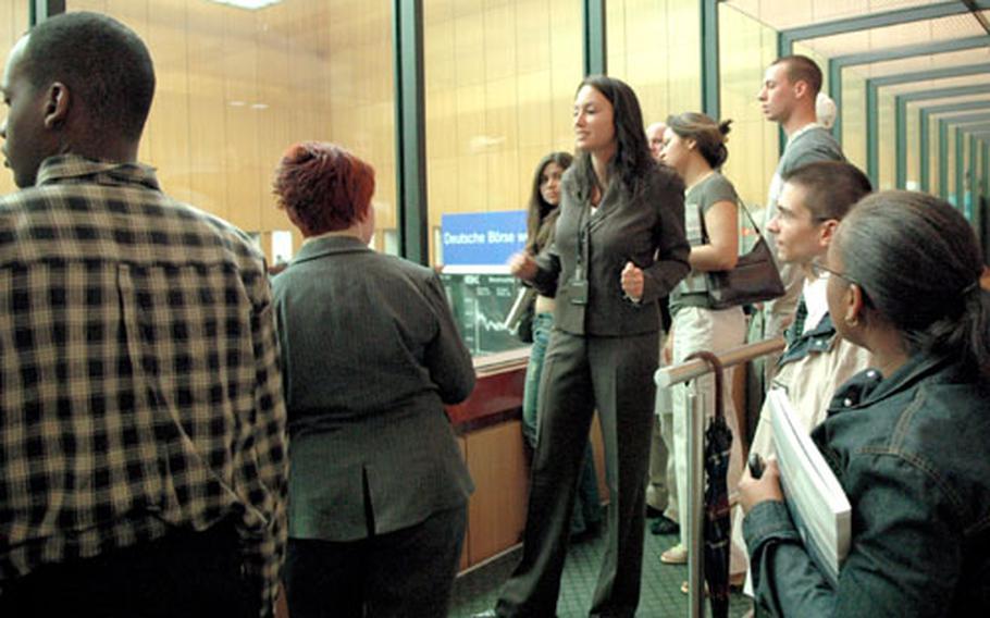 Rebecca Schmidt, center, of the Deutsche Börse legal department explains the Frankfurt stock exchange floor to University of Maryland students during their tour of the exchange.