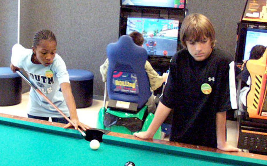 Marcel Tibbs lines up a shot on the pool table while Phillip Brady watches Thursday shortly after the ribbon cutting for the $7.4 million youth center at Aviano Air Base. The 31,000-square-foot facility is now the hub of out-of-school activities for youth on base.
