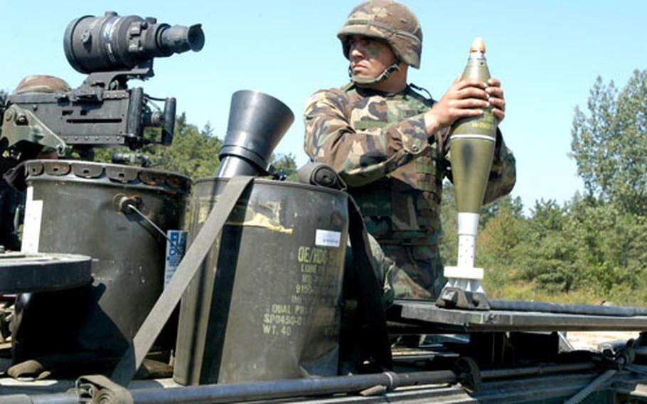 Pvt. Jacob Holden, 20, of Seattle prepares to load a mortar round.