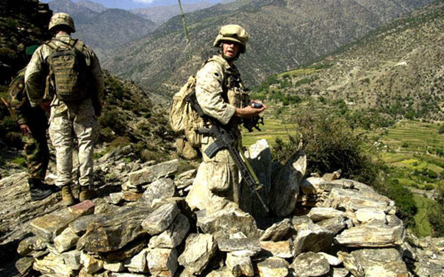 U.S. Marine Cpl. Brandon Fields examines an enemy fighting position on a mountainside Thursday afternoon in eastern Afghanistan's Kunar province. Marines from 3rd Platoon, Company E, 2nd Battalion of the 3rd Marine Regiment, 3rd Marine Division, climbed the mountain in search of four men believed to be carrying weapons.