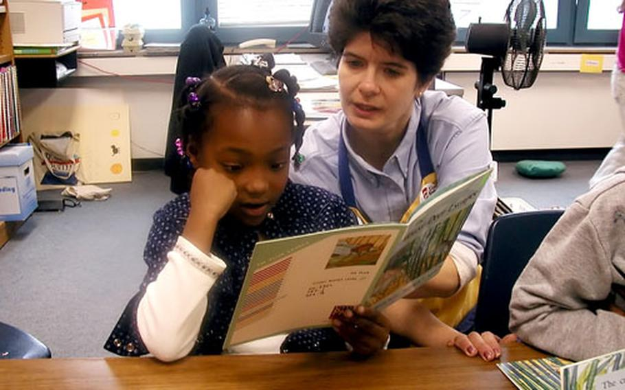 Lisa Heinzmann, a teacher at Kitzingen Elementary School, helps a student sharpen her reading skills in this 2002 photo. The school is one of three in the Würzburg-Kitzingen community that will be closing at the end of the current school year as part of the move of 1st Infantry Division troops to the States.