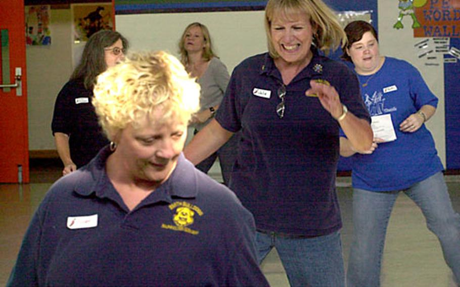 """File line-dancing under """"it looks easier than it is."""" Julie Lindke, a third-grade teacher at Smith Elementary, wasn't the only teacher who had trouble remembering the long step sequences. Line-dancing was one of about a dozen offerings at Wetzel Elementary during Friday's in-service day, which brought both schools' staffs together."""