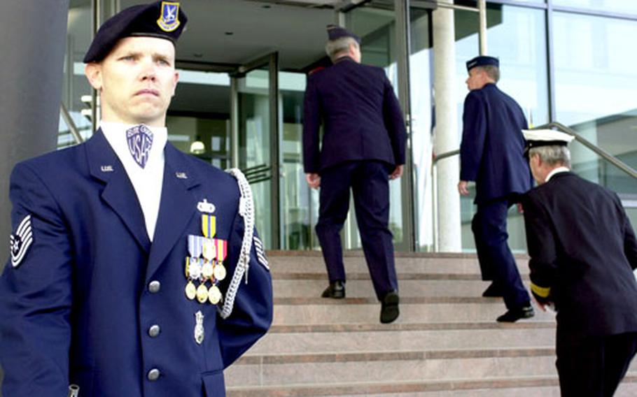 A U.S. Air Force elite guard member stands at the foot of the front entrance to the Aillied Air Component Command headquarters.