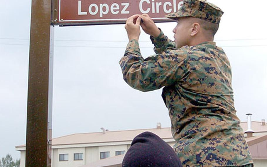 """Capt. Roberto Ibaita, with Marine Air Control Group-18, from Okinawa, Japan, unveils the """"Lopez Circle"""" street sign at Camp Humphreys in Pyeongtaek. The base plans to honor key figures, organizations and equipment from the history of the U.S.-South Korean alliance."""