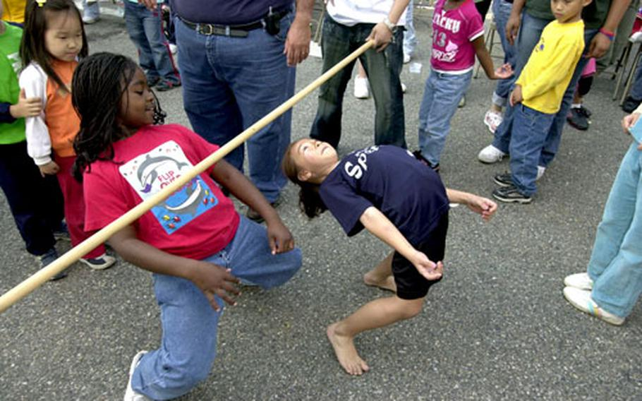 Six-year-old Ashley Gattis, right, works her way through the competition during the limbo contest Saturday.