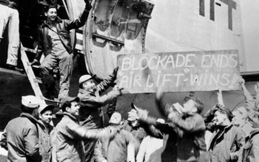 """U.S. Navy Squadron VR-6 is greeted at Rhein-Main Air Base on its arrival on May 12, 1949. The sign reads """"Blockade ends airlift wins."""""""