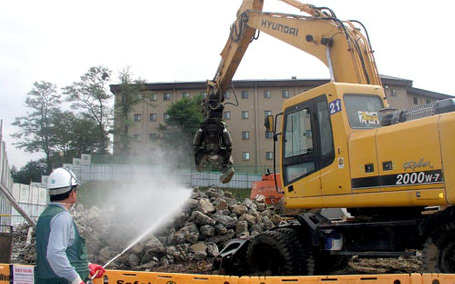 A worker trains a hose on a rubble pile during preparation last week of a site where an apartment building will go up. It'll become part of a three-building family housing complex set for completion in 2008.