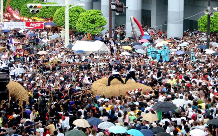 Leaders of the Nishi, or West, side in Sunday's Great Naha Tug-of-War urge their members to pull the eyelet of their part of the 43-ton rope toward the Higashi, or East, side's eyelet to make the knot creating the world's largest rice straw rope.