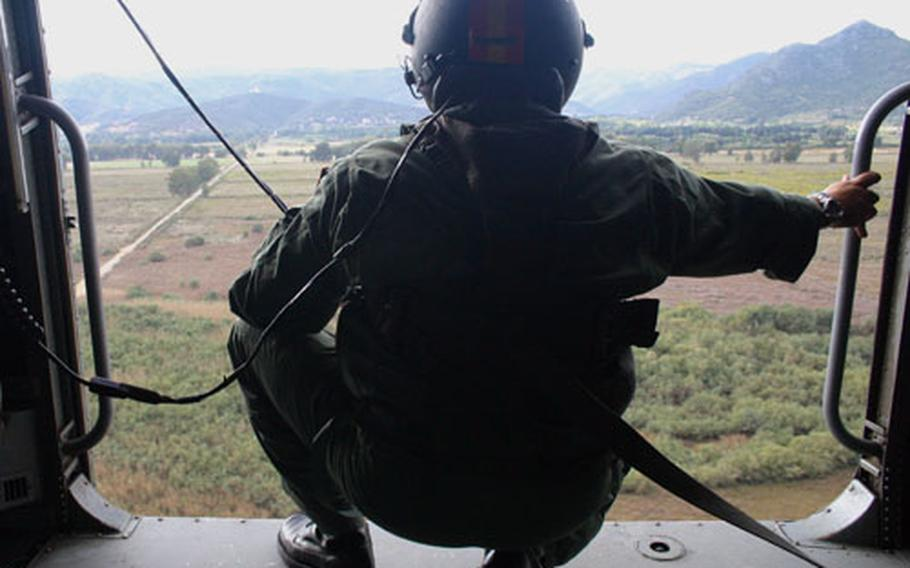Rafael Orellana Ortega of the Spanish navy surveys the Sardinian landscape Friday from the open door of a SH-3D Sea King helicopter during the multi-NATO nation exercise Destined Glory (Loyal Midas) 2005.