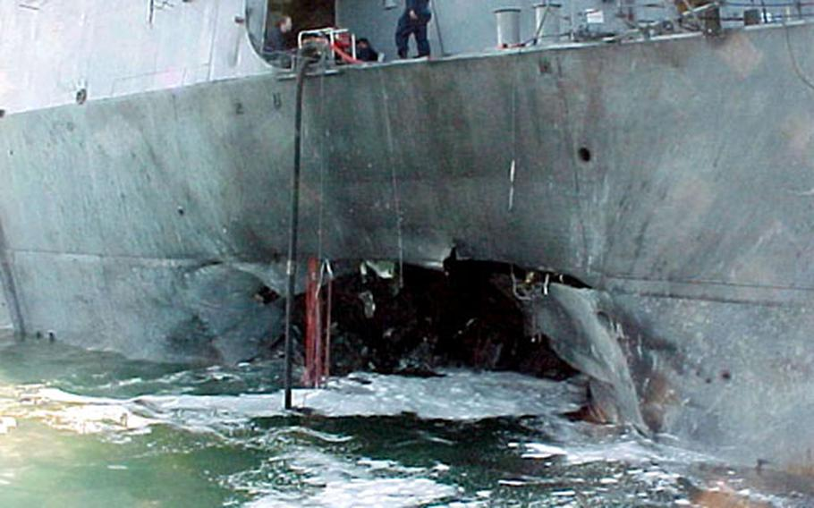 Port-side view showing the damage sustained by the Arleigh Burke-class guided missile destroyer USS Cole after a terrorist bomb exploded on Oct. 12, 2000, during a refueling operation in the port of Aden, Yemen.