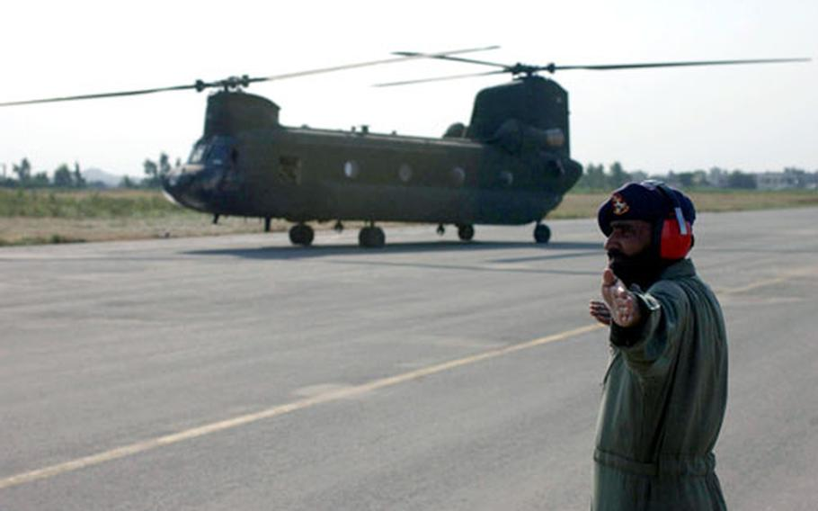 A Pakisani Soldier directs U.S. helicopters as they touch down on Qasim Army Airfield in Pakistan. The Germany-based helicopters flew from Afghanistan to provide earthquake relief. (enw# 61p pp)