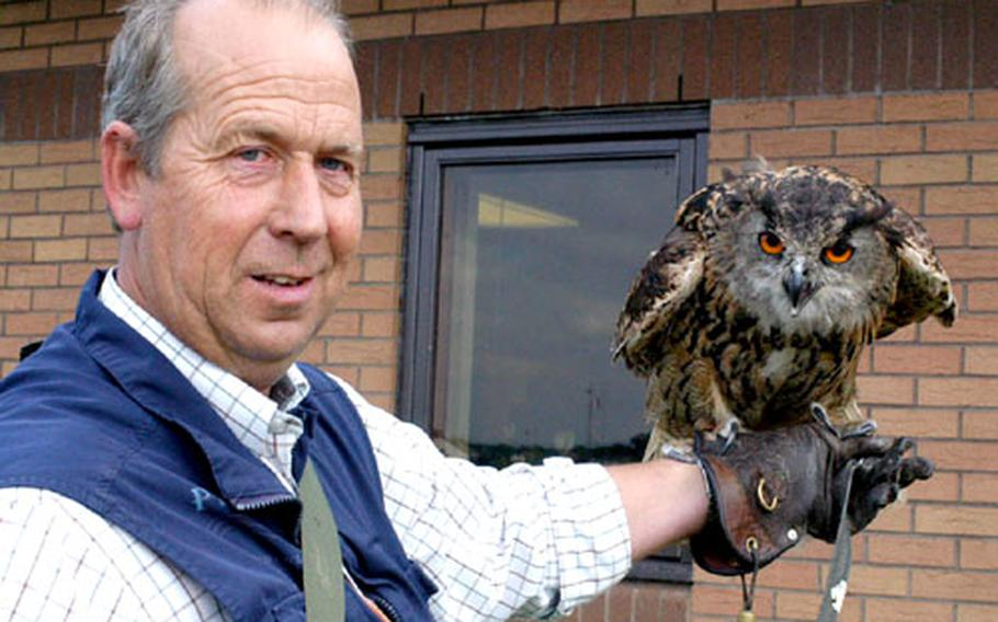 Keith Mutton, owner and operator of Phoenix Bird Control Services, stands with one of his oldest employees, Twinkle, a 17-year-old European eagle owl. Twink, as he calls her, responds to voice commands, and even recognizes her own name.