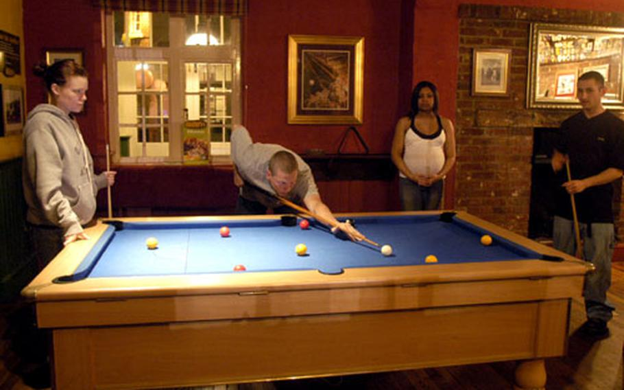 Jason Daffern makes a shot while playing eight-ball billiards at the Bird in Hand pub near RAF Mildenhall recently. With Daffern are, from left, wife Jen, and Rosemary and Philip Harville.