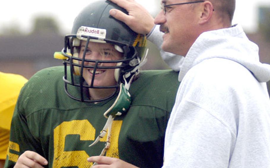 Alconbury High School offensive lineman Sarra Stanley gets a pat on the helmet from offensive coordinator Rodney Lucas during a recent practice.