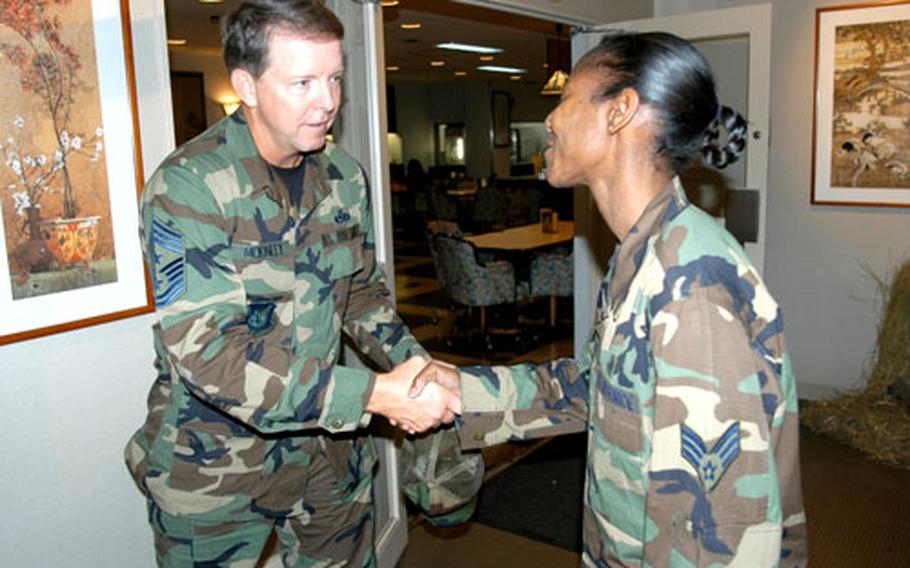 Pacific Air Forces Command Chief Master Sgt. Rodney J. McKinley shakes hands with Senior Airman Nekia Mbaye after giving her a coin during his visit to Misawa Air Base, Japan, last week. Mbaye, of the 35th Aerospace Medical Squadron, was named the top 2004 bioenvironmental technician in the Air Force.