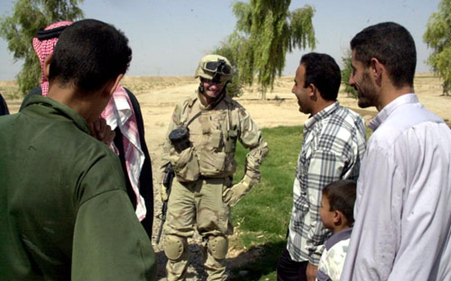 Lt. Blaine Sellman, of the 1st Brigade Troops Battalion, 3rd Infantry Division, talks with rural Iraqis living near Forward Operating Base Speicher on Friday. Iraqis will vote on the draft constitution Saturday.