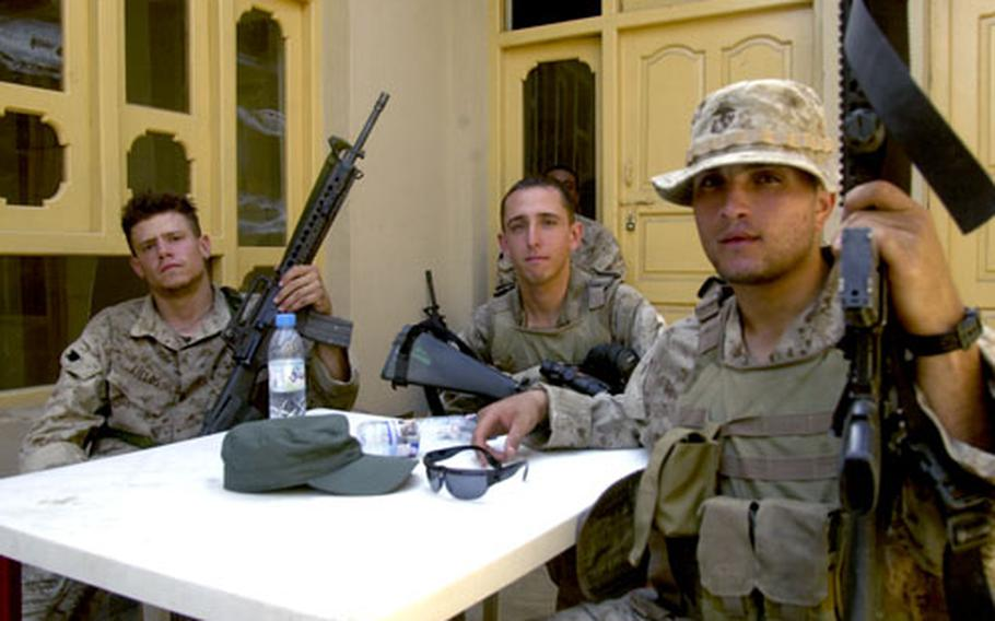 U.S. Marine Corps Cpl. Brandon Fields, left, Lance Cpl. Larry Gonzales, center, and Cpl. Jason Stout, right, relax at a patrol base after spending several days on patrol in eastern Afghanistan.