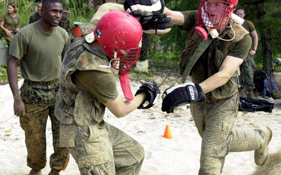 """Lance Cpl. Randy Anderson, a military police patrolman from MCAS Futenma, makes a """"killing blow"""" to his opponent's head with a rubber knife during hand-to-hand combat training on Camp Schwab Tuesday. Staff Sgt. Antonio Mitchell, left, watch commander at MCAS Futenma, supervises for safety."""