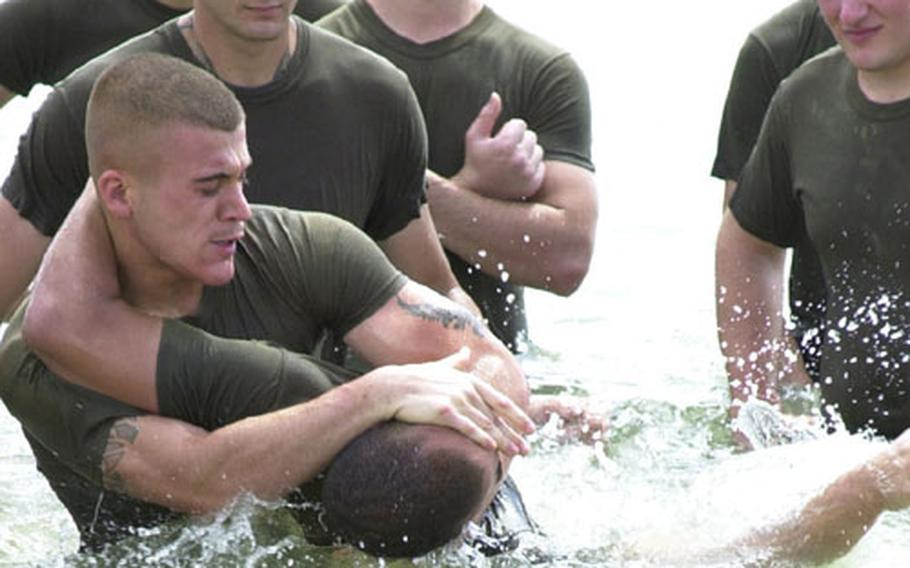 """Lance Cpl. Roberto Soares, military police patrol supervisor on Camp Foster, """"chokes out"""" Lance Cpl. Timothy Richardson, a patrolman at MCAS Futenma, during a grappling training session in the water just off the beach of Camp Schwab Tuesday."""