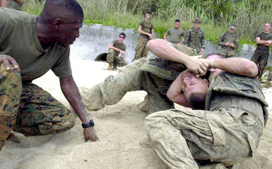 Staff Sgt. Antonio Mitchell, left, watches as Lance Cpl. Roberto Soares get choked by Lance Cpl. Sean Wilkinson during a grappling training session involving military policeman on the beach of Camp Schwab Tuesday.