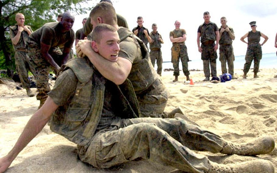 Pfc. Joseph Maness, a military police patrolman from Camp Courtney, is put in a choke hold by fellow Camp Foster patrolman Lance Cpl. Jonathan Tufo during a grappling training session.