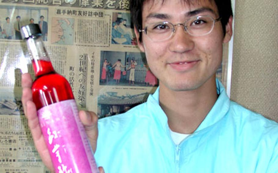 Go Miyagi, a member of the Sweet Potato Festival committee, holds Kadena town's new product, sweet potato vinegar.