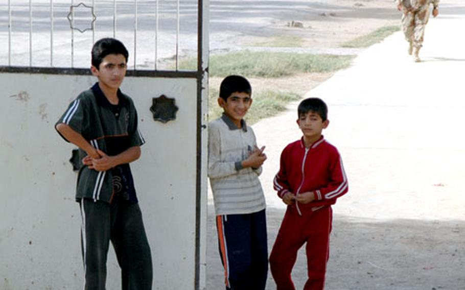 """Schoolboys in Tabi """"guard"""" their school, which will be an election site. The boys said they were happy about the election, because school had been cancelled the day prior to the vote."""
