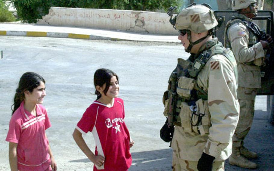 Spc. Joshua Hines, 25, of Conway, Ark., talks with children in Samarra outside of the city mayor's office on Wednesday.