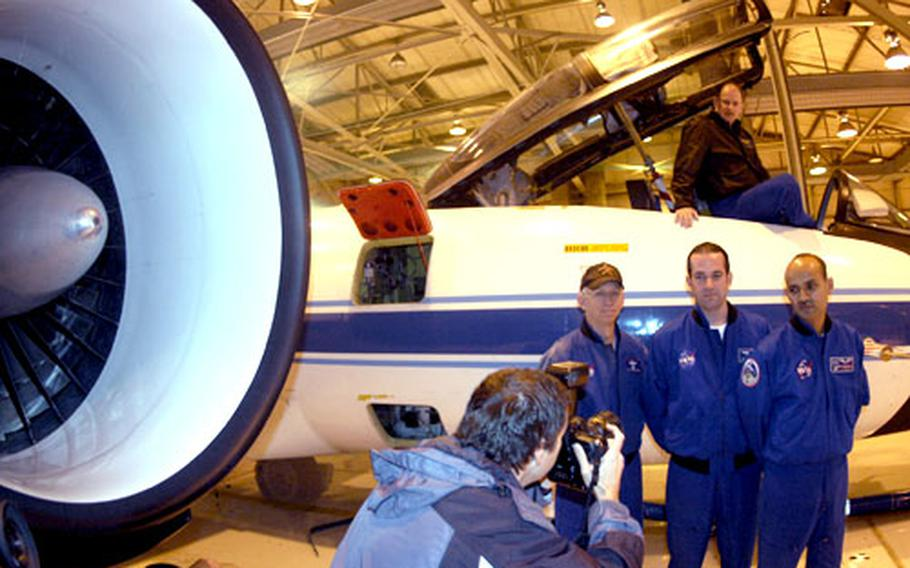 NASA WB-57 flight members pose for a photo at RAF Mildenhall. Sitting in the cockpit is pilot Scott Reagan. Standing are, from left, pilot Bill Ehrenstrom and systems equipment operators Brian Barnett and Tushar Suthar.