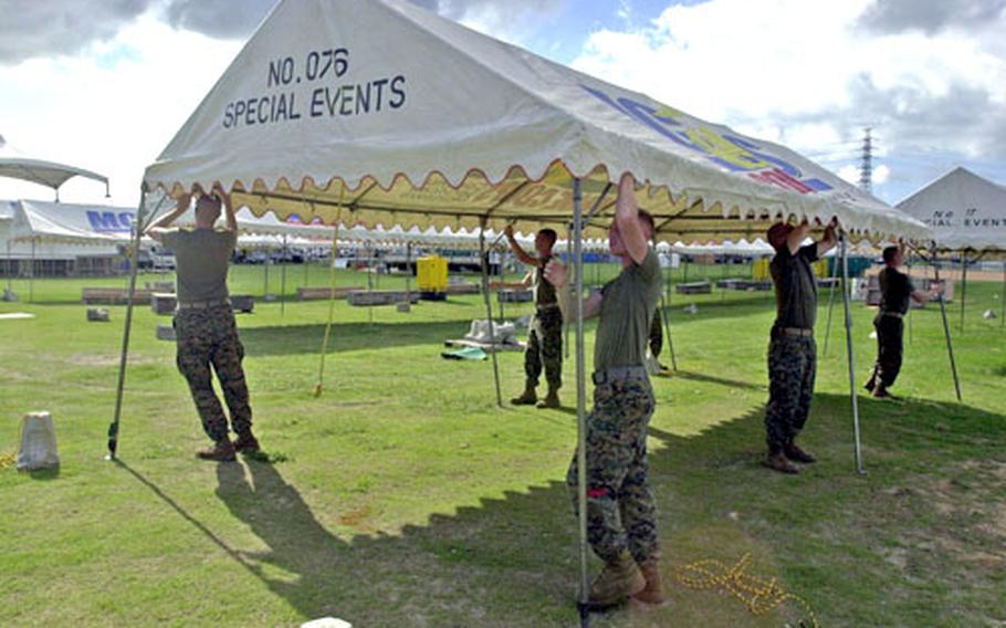 A working party of Marines raise one of many canopies on the Camp Foster parade field in preparation for this weekend's Foster Fest.