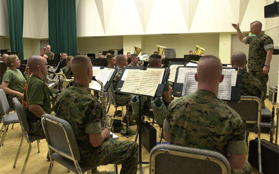 Chief Warrant Officer 2 Benjamin Bartholomew, right, leads the III Marine Expeditionary Force Band during a rehearsal for Friday's Combined Concert at the Ginowan Convention Center.