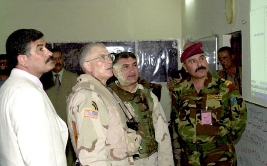 Task Force Liberty Commander Maj. Gen. Joseph Taluto reviews the voter tally with Salah Ad Din province Gov. Hamad Hmood Shigti, left, and Iraqi Brig. Gen. Abdul Jabar Salih, right, at the Provincial Joint Coordination Center on Saturday.