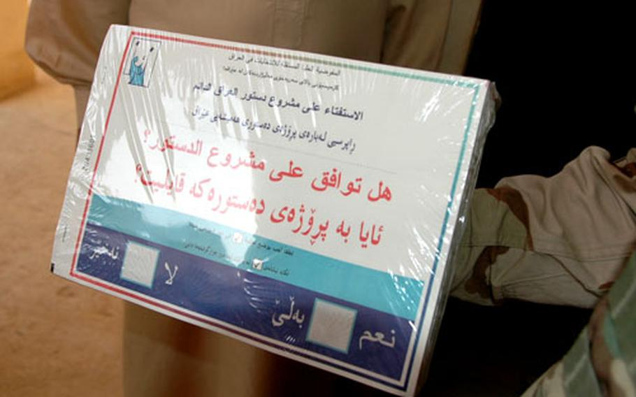 Poll workers at a polling place in Tabi show off the ballot for the national constitutional referendum.