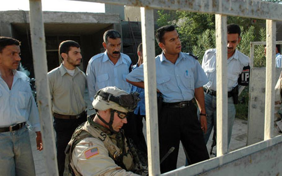 First Lt. Robert Peterson confers with Iraqi police and voting officials at a polling place in Muqdadiyah. Peterson was checking on final security precautions Friday.