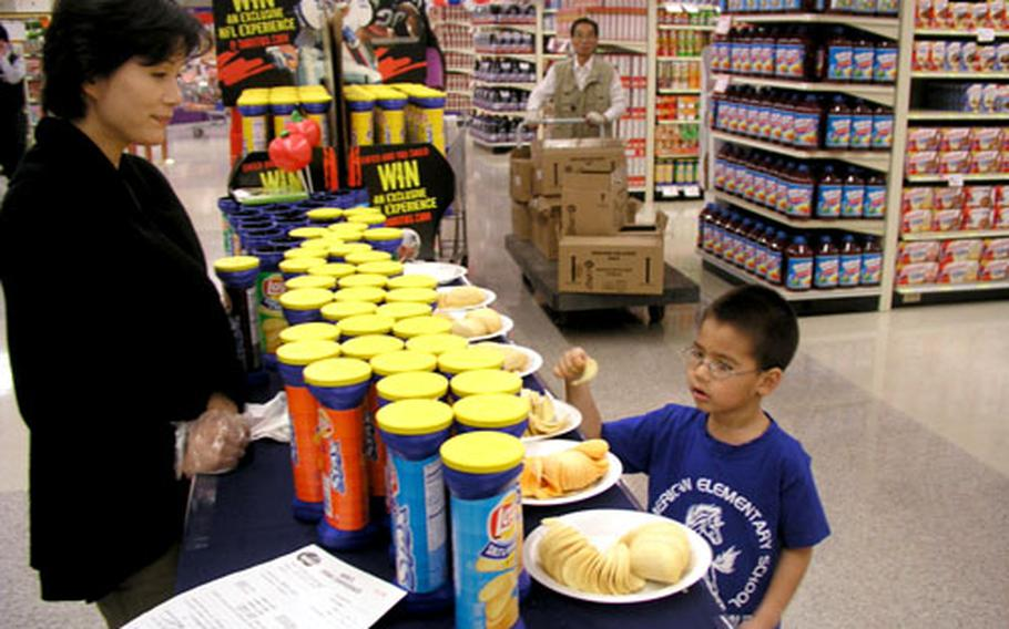 A youngster samples a free chip at the newly renovated Osan Air Base commissary in South Korea on Friday afternoon. Officials marked the completion pf the project with a brief ceremony and merchandise giveaways.